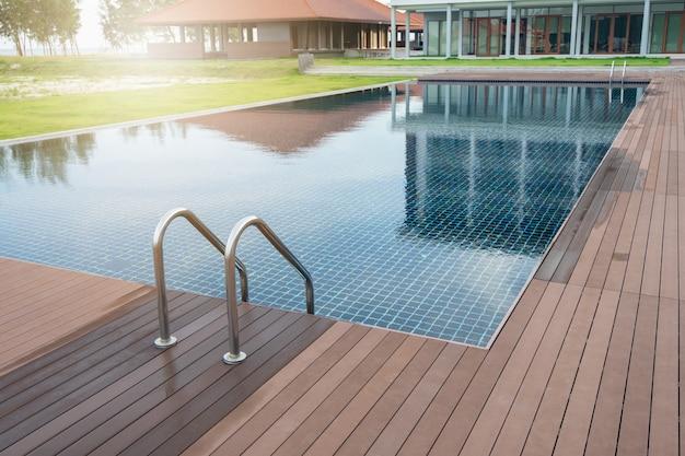 Zwembad bij hotel met trap en houten dek op het strand