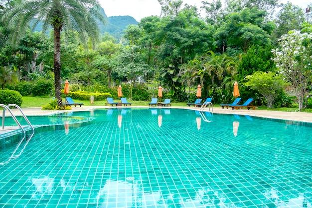 Zwembad in tropisch resort met strandstoelen