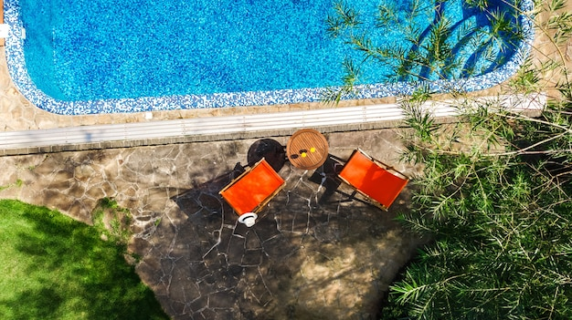 Zwembad met blauw water en zonnebank ligstoelen luchtfoto bovenaanzicht tropische vakantie hotel resort