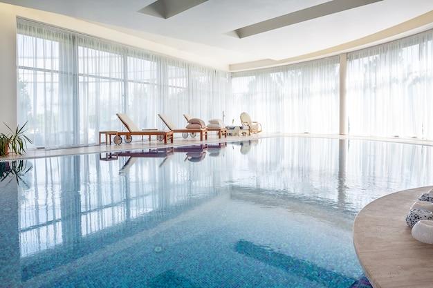 Zwembad met houten ligstoelen en rieten schommelstoel in ruime kamer van luxe herenhuis
