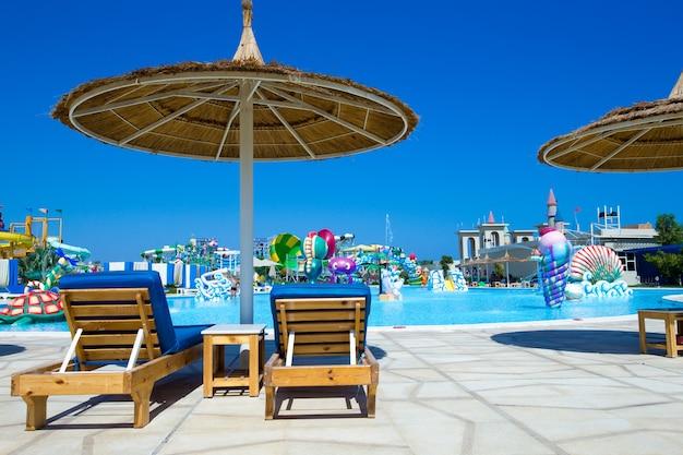 Zwembad met kokospalm en witte parasol