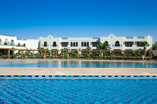 Zwembad met kokospalmen en witte parasols en hotel
