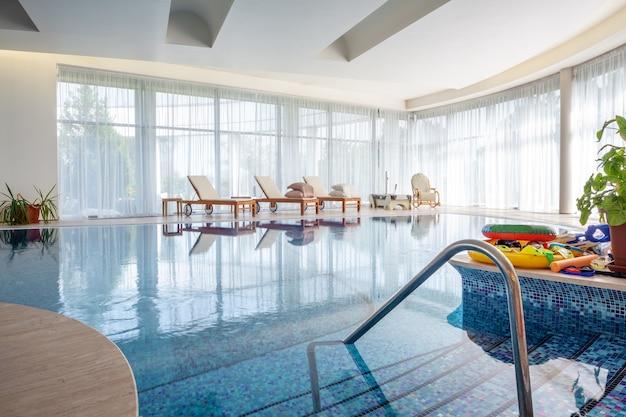Zwembad met ligstoelen en schommelstoel in ruime kamer van privé landhuis