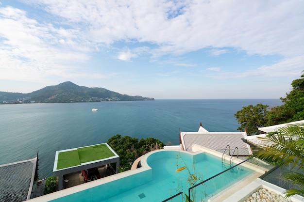 Zwembad met trap bovenop dakterras met uitzicht op tropische zee, luxe strandvillahuis met zwembad met zeezicht in modern design, zomervakantie en reisachtergrondconcept.