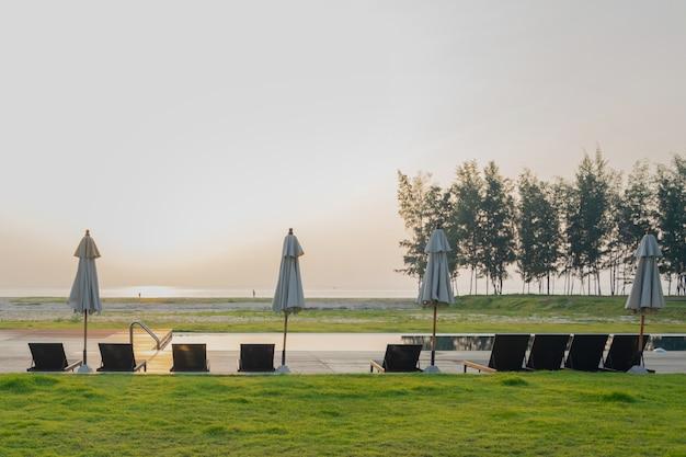 Zwembad met twee ligbedden, ligstoelen, parasol in het strandresort