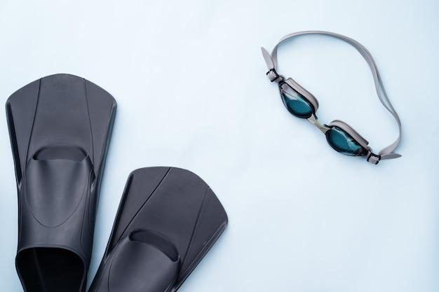 Zwembril en flippers op blauwe achtergrond. concept van zwemmen