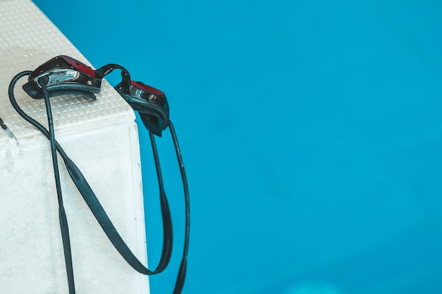 Zwembril zit op de borstwering bij het zwembad