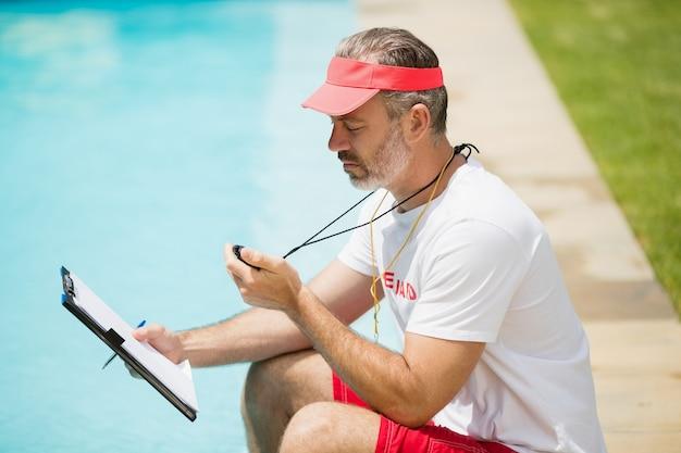 Zwemcoach die stopwatch bij het zwembad bekijkt