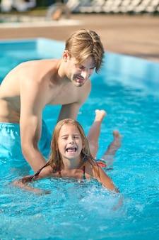 Zwemlessen. een jonge vader die zijn dochter leert zwemmen
