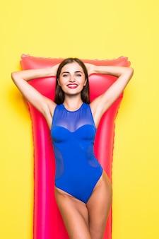Zwemmen is leuk. vrolijk jong meisje die met opblaasbare matras gele muur gaan peilen