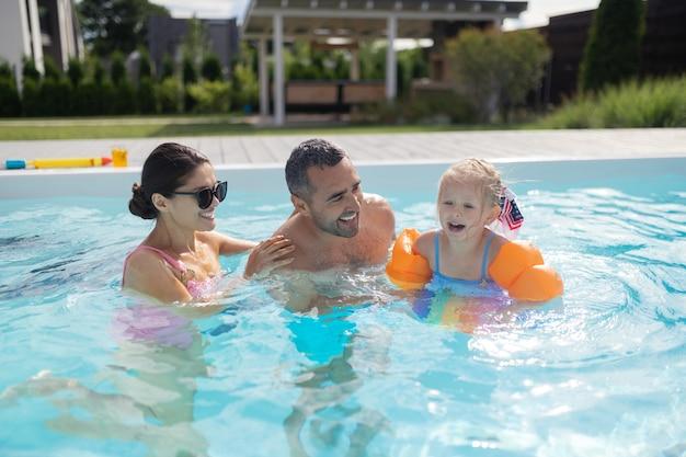 Zwemmen met ouders. schattige blonde meid voelt zich opgewonden en geweldig tijdens het zwemmen met ouders