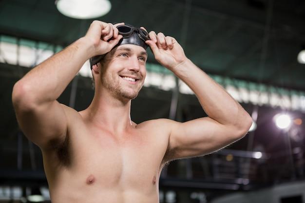 Zwemmer draagt een zwembril en pet