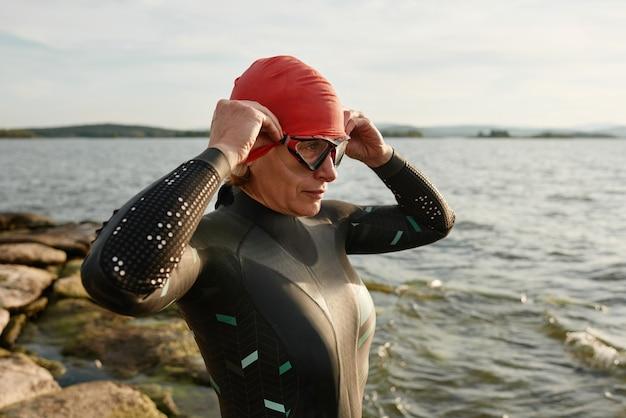 Zwemmer in zwembroek die een veiligheidsbril opzet voordat hij in het meer gaat zwemmen