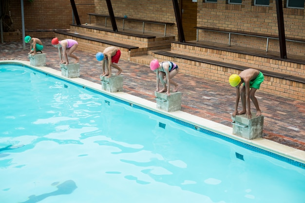 Zwemmers die zich voorbereiden om weg te duiken vanaf het startblok bij het zwembad