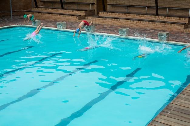 Zwemmers opspattend water tijdens het duiken in het zwembad