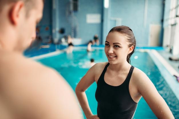 Zwemmers praten over training tegen zwembad
