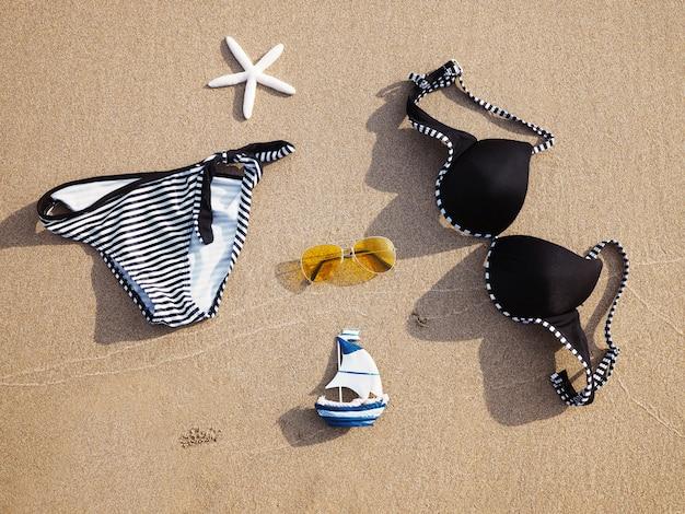 Zwempak en zonnebril op zand bij zonsondergangstrand.