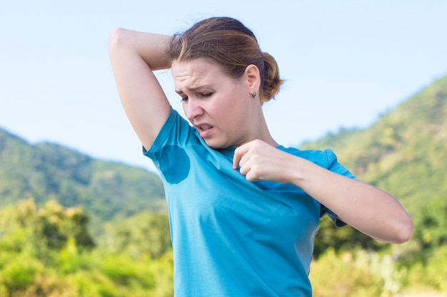 Zwetend jong meisje snuffelend aan haar oksel, kijkend naar de plek, zweetvlek op haar t-shirt met walging emotie, gezicht, frons. boos gefrustreerde vrouw die lijdt aan hyperhidrose. zonnige warme zomerdag
