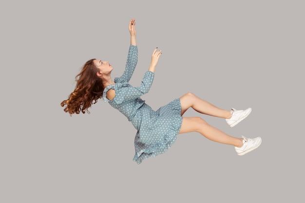Zwevend in de lucht. ontspannen mooi meisje ruches jurk en krullend stijgend haar zwevende, vliegen in droom met handen omhoog, reikend naar iets hoogs. indoor studio-opname geïsoleerd op een grijze achtergrond