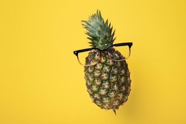 Zwevende ananas met een bril op een gele achtergrond met kopieerruimte