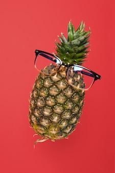 Zwevende ananas met een bril op een rode achtergrond met kopieerruimte