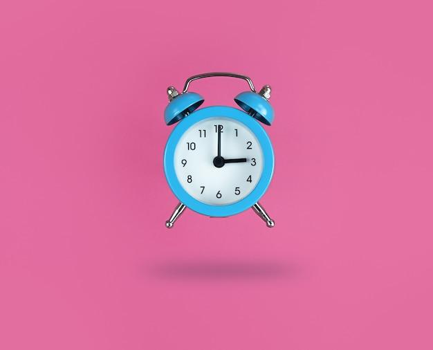 Zwevende blauwe wekker op een roze achtergrond.