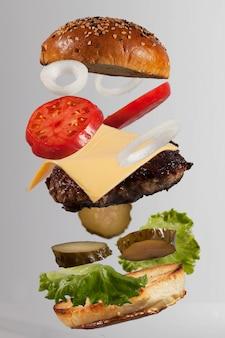 Zwevende verse en mooie cheeseburger-ingrediënten
