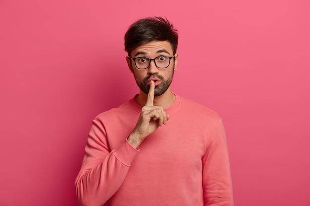 Zwijg, alsjeblieft. benieuwd verrast man eist stilte, verbiedt spreken, houdt wijsvinger tegen de lippen gedrukt, kijkt verrassend door een bril, vraagt geen geruchten te verspreiden, geïsoleerd op roze muur