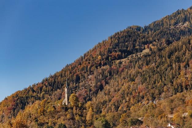 Zwitserland, bergkerk op de achtergrond van alpiene bergen en landschapsbomen
