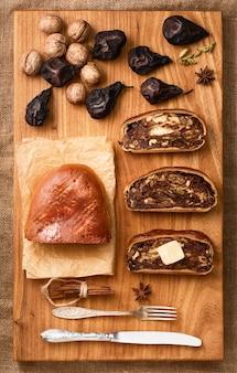 Zwitsers perenbrood - birnbrot. lokaal gebakken goederen gevuld met gedroogde peren, noten en fruit. bovenaanzicht van vers gebakken perenbrood in plakjes gesneden, naast boter. feestelijk ontbijt