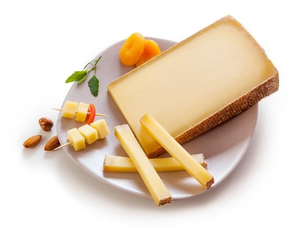 Zwitserse gruyère-kaas in een plaat op witte achtergrond