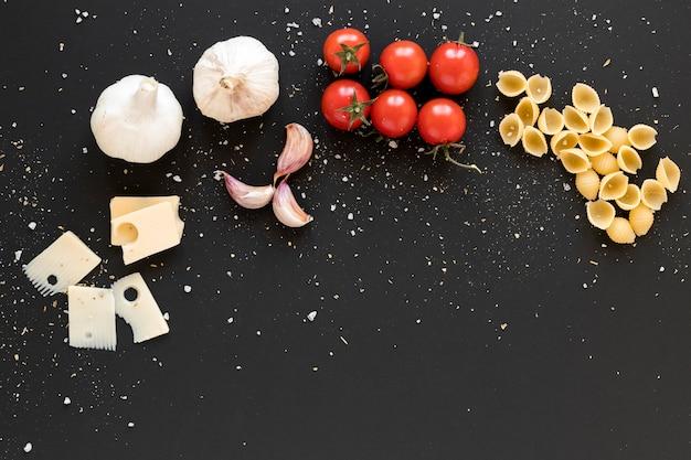 Zwitserse kaas; knoflook; cherry tomaat en conchiglie pasta op zwarte achtergrond