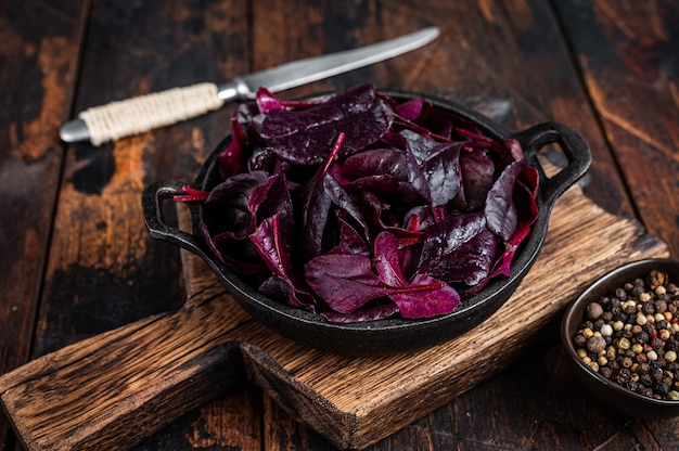 Zwitserse rode snijbiet of mangold salade leafs in een pan. donkere houten achtergrond. bovenaanzicht.