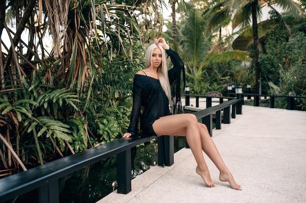 Zwoele langharige blonde ik met mooie lange benen zittend op een bankje