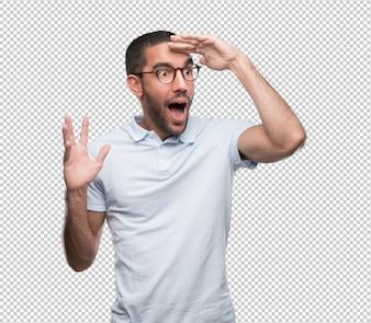 Verbaasde jonge man met een gebaar van ver kijken met zijn hand