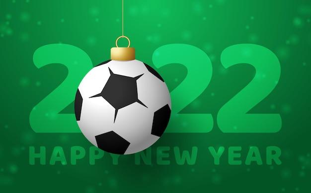 2022 gelukkig nieuwjaar. sport wenskaart met een voetbal voetbal op de luxe achtergrond met sneeuwvlok. vector illustratie.