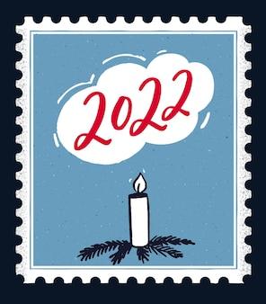 2022 wenskaart ontwerp. rode handgeschreven nummers op blauwe stempelachtergrond met handgetekende kaars versierd met kerstboomtakken
