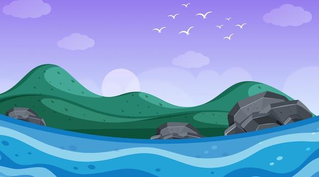 Aardscène met oceaan en heuvels