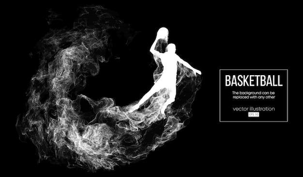 Abstract silhouet van een basketbalspeler op donkere zwarte achtergrond van deeltjes, stof, rook, stoom. de basketbalspeler wordt uitgevoerd.