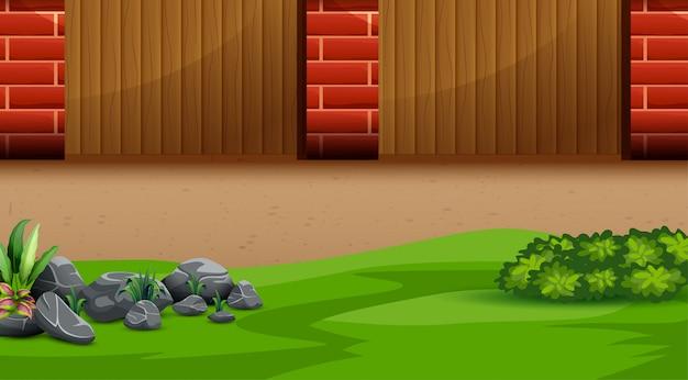Achtertuin met houten hek, bakstenen pilaren en groen gras