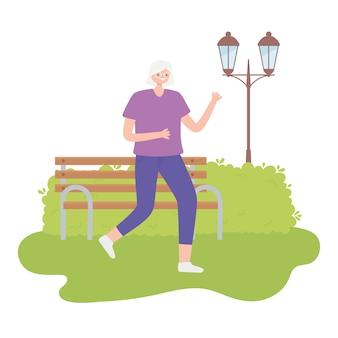 Activiteit senioren, rijpe vrouw met sportkleding wandelen in de park-afbeelding