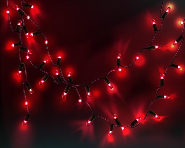 Afbeelding van kerstmisslinger met rode gloeilampen geïsoleerd op donkere achtergrond met ruimte voor tekst