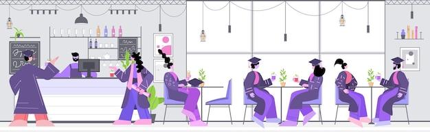 Afgestudeerde studenten bespreken tijdens bijeenkomst in café afgestudeerden vieren academisch diploma graad onderwijs online communicatieconcept restaurant interieur horizontaal volledige lengte