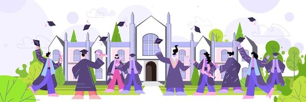 Afgestudeerde studenten die hoeden gooien in de buurt van universiteitsgebouw afgestudeerden vieren academisch diploma onderwijsconcept volledige lengte horizontaal