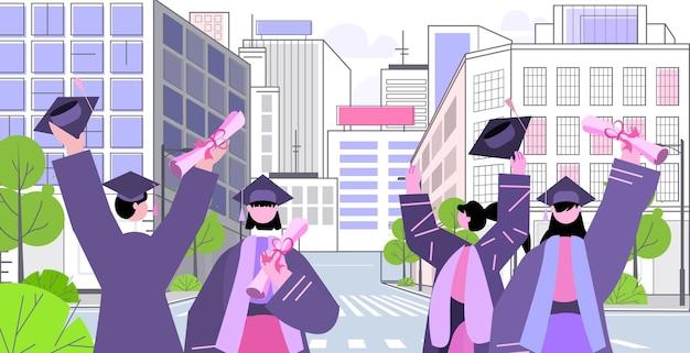 Afgestudeerde studenten op straat afgestudeerden vieren academisch diploma graad onderwijs concept stadsgezicht achtergrond portret horizontaal