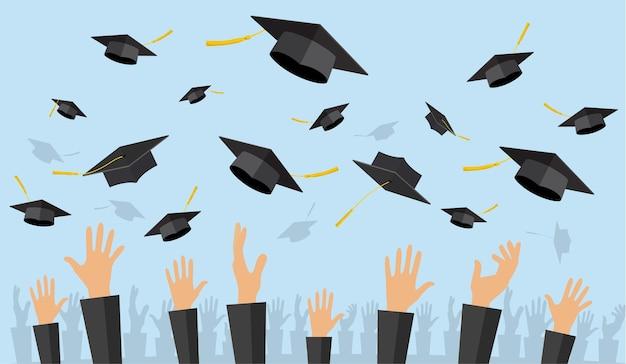 Afgestudeerde studenten van leerling handen in jurk afstuderen caps in de lucht gooien