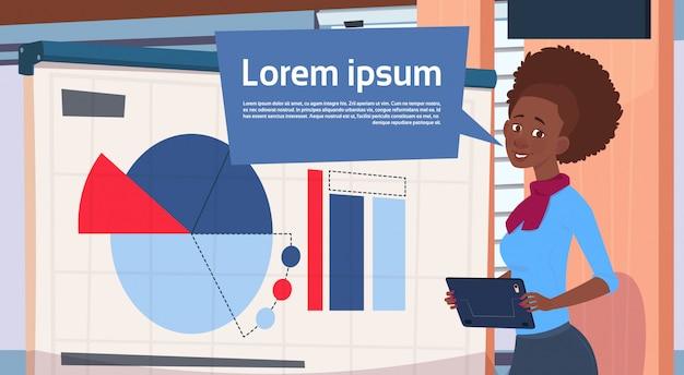 African american zakenvrouw holding presentatie stand over boord met grafieken en grafiek bedrijf