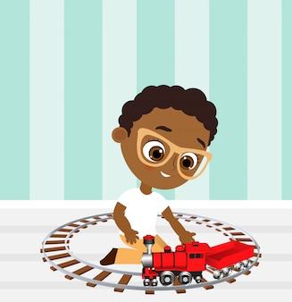 Afrikaanse amerikaanse jongen met glazen en stuk speelgoed trein. jongen speelt met de trein