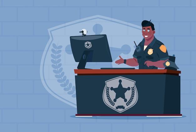 Afrikaanse amerikaanse politieagent die aan computer werken die eenvormige cop in wachtkantoor dragen over baksteenachtergrond