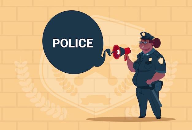 Afrikaanse amerikaanse politievrouw planningsactie inzake witte raad die eenvormige vrouwelijke wacht op blauwe bakstenenachtergrond draagt